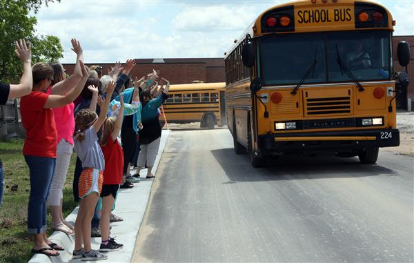 Staff members waive to the buses as they depart school.