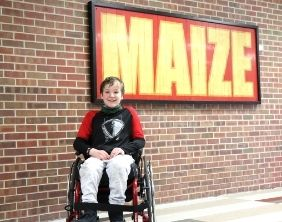 Noah Rankin posing in front of a Maize sign